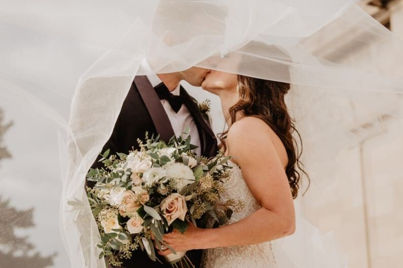 Bride and Groom Kissing Under a the Bride's Veil