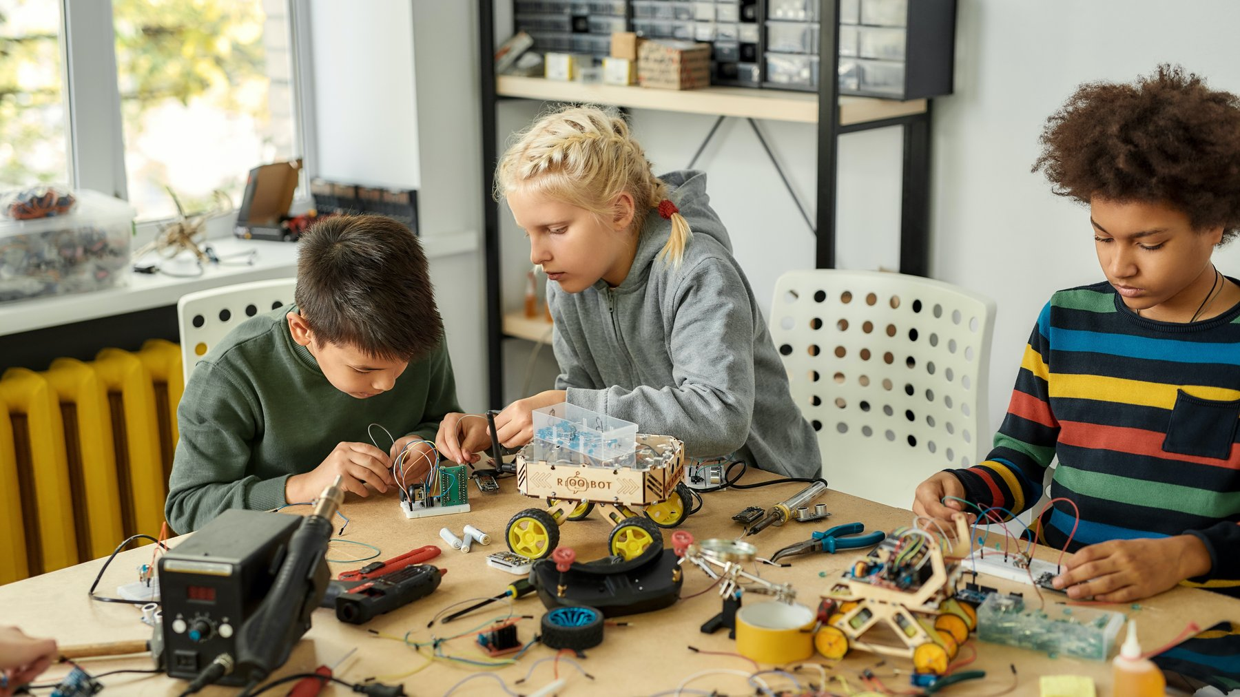 Three kids creating STEM projects together.